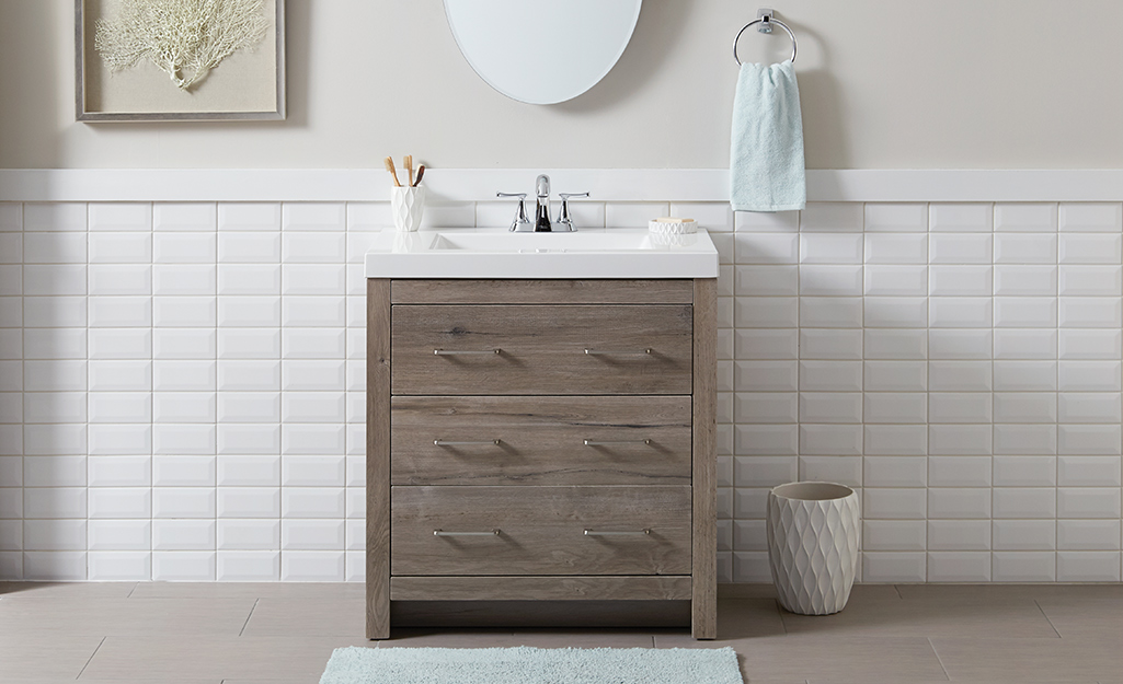 Farmhouse Style Bath Vanity With A White Top Agains Tile Wall In Bathroom