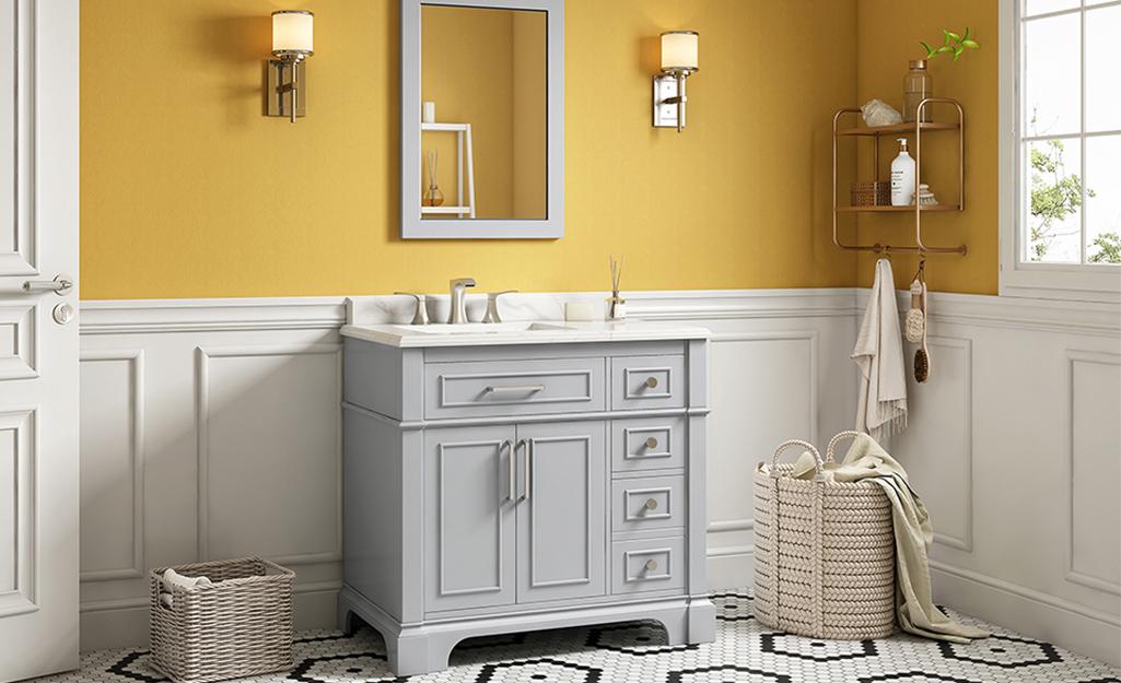 Bàn trang điểm độc lập màu xám giữa giỏ đan trong phòng tắm với bức tường màu vàng mù tạt.