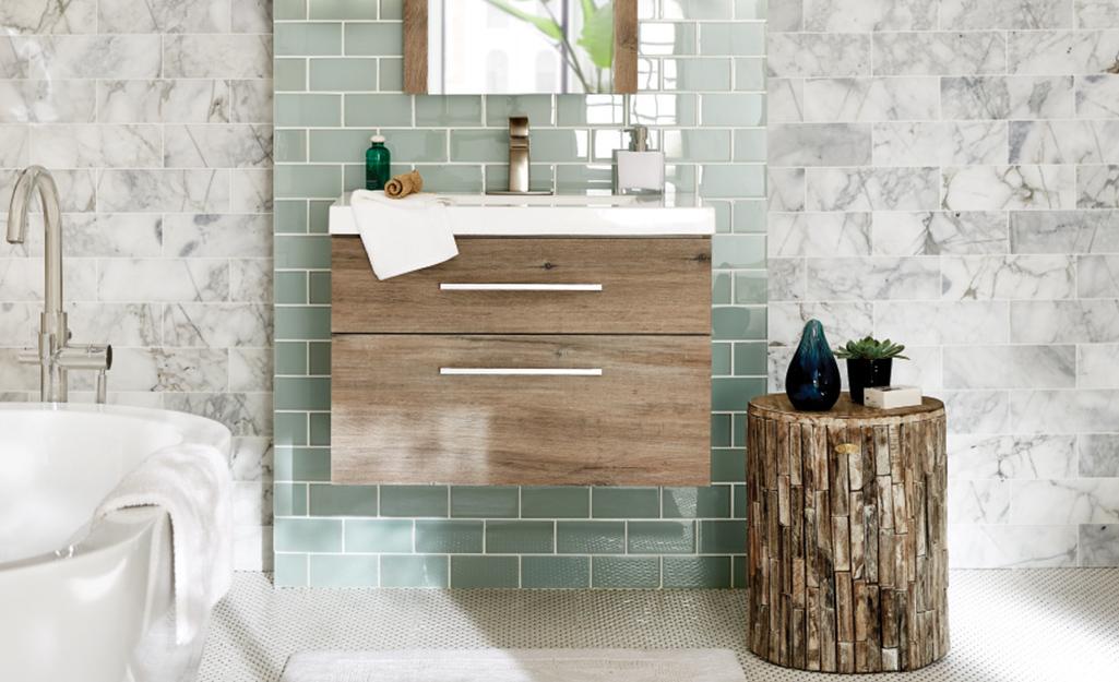 Bàn trang điểm nổi bằng gỗ sáng màu với hai ngăn kéo gắn vào tường gạch xanh.
