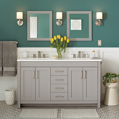 A light grey furniture-style bath vanity with two round mirrors on the wall above it.