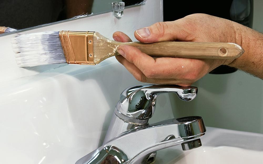 Một người vẽ bàn trang điểm trong phòng tắm.