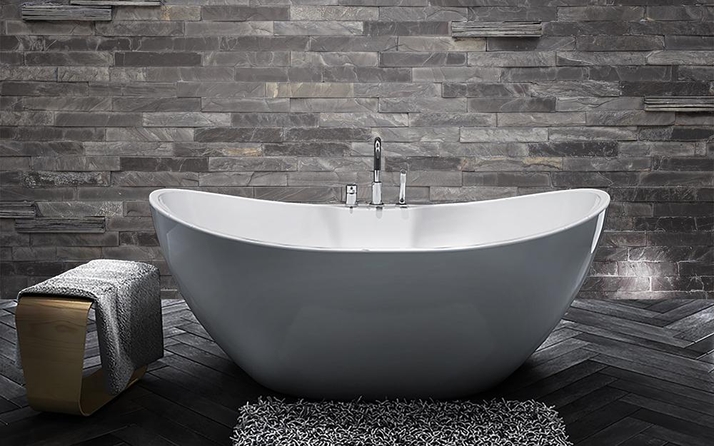 Một bồn tắm có chân đế màu trắng với các cạnh cong nằm phía trước bức tường lát đá xám