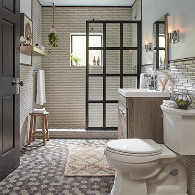 A bathroom features patterned floor tile and a paned glass shower door