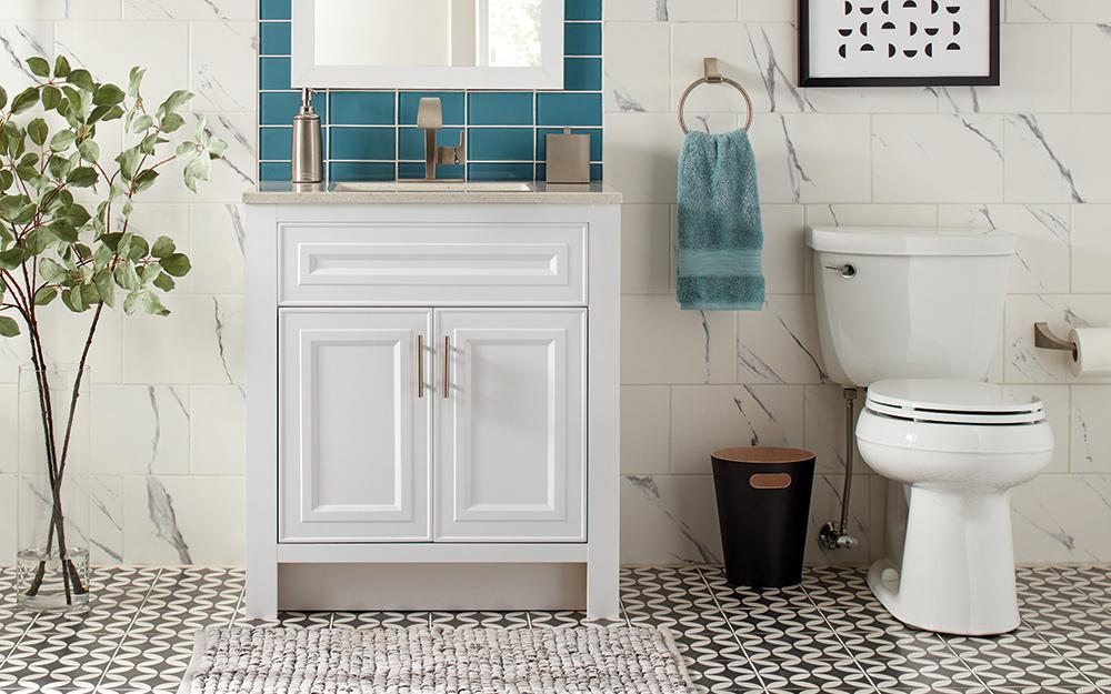 Vanity resting on black and white tiles on a bathroom floor.