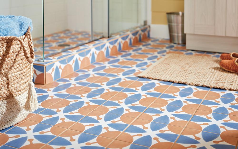 Blue, orange and white patterned floor tile in a bathroom.
