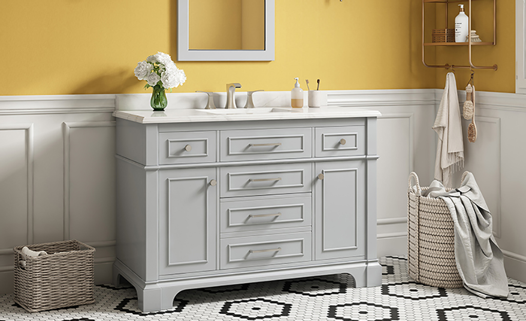 A gray bathroom vanity in a yellow bathroom with white wainscoting.