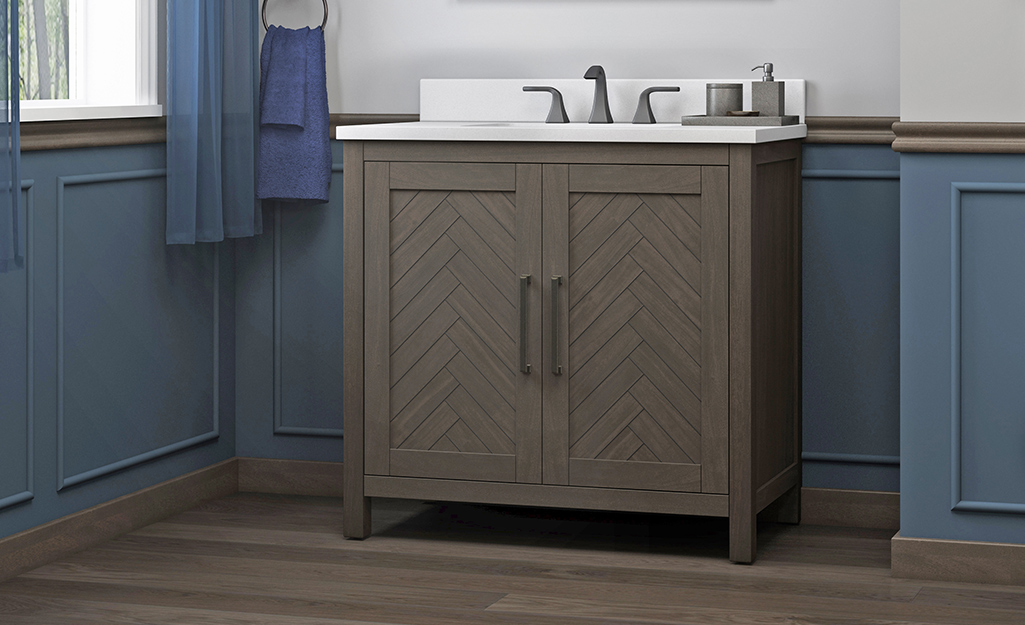 A farmhouse bathroom vanity with herringbone cabinet doors.