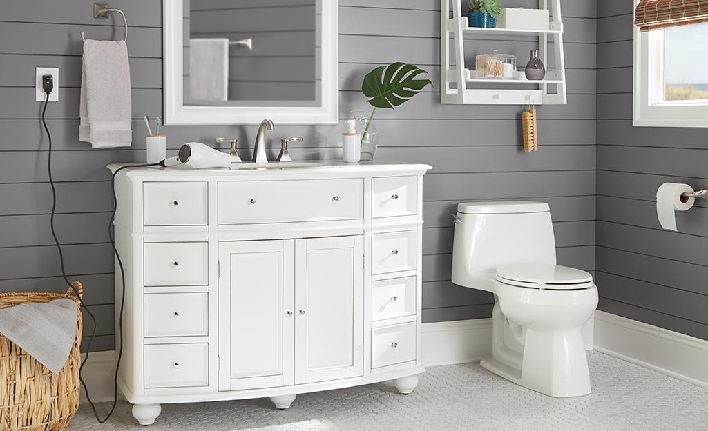 A white furniture-style coastal vanity in a gray wood-paneled bathroom.