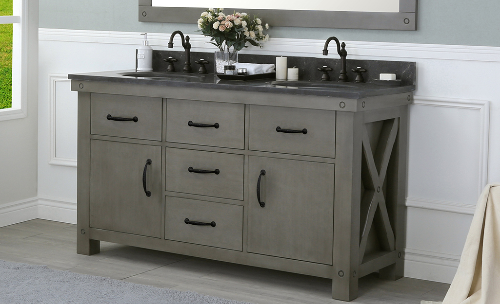 A distressed gray industrial bathroom vanity with rustic detailing and a dark countertop.