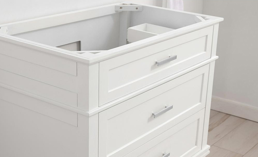 A white bathroom vanity without a countertop or sink.