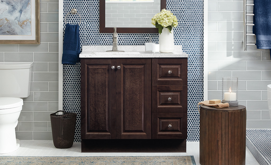 A brown cabinet vanity with a door and two drawers.