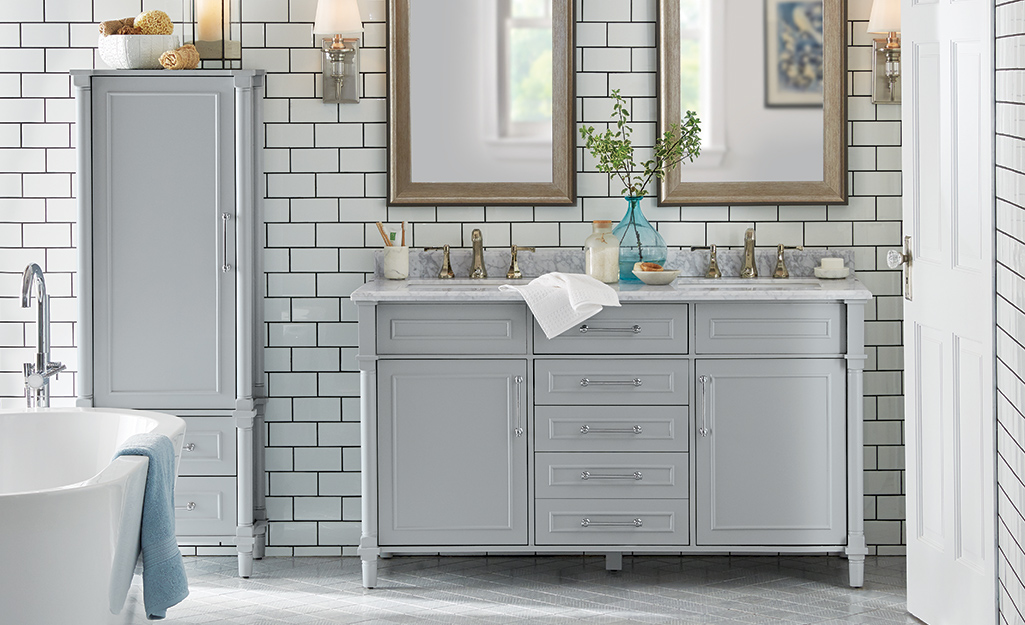 A gray double sink vanity in a large master bathroom.