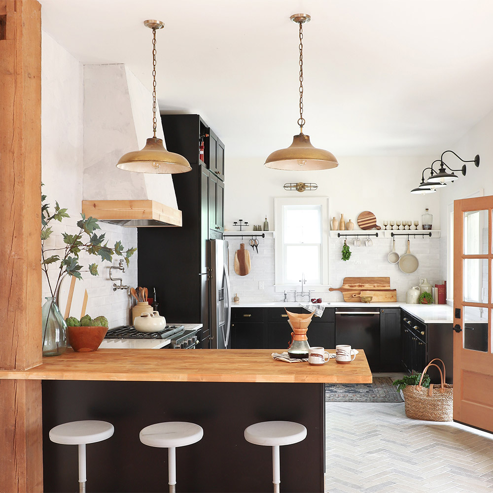 A kitchen with herringbone floors, black cabinets and wood accents.