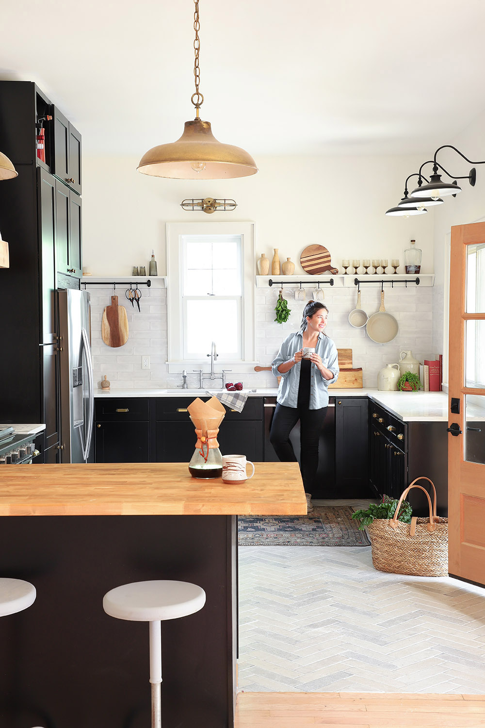 A woman standing in an updated kitchen filled with bright light.