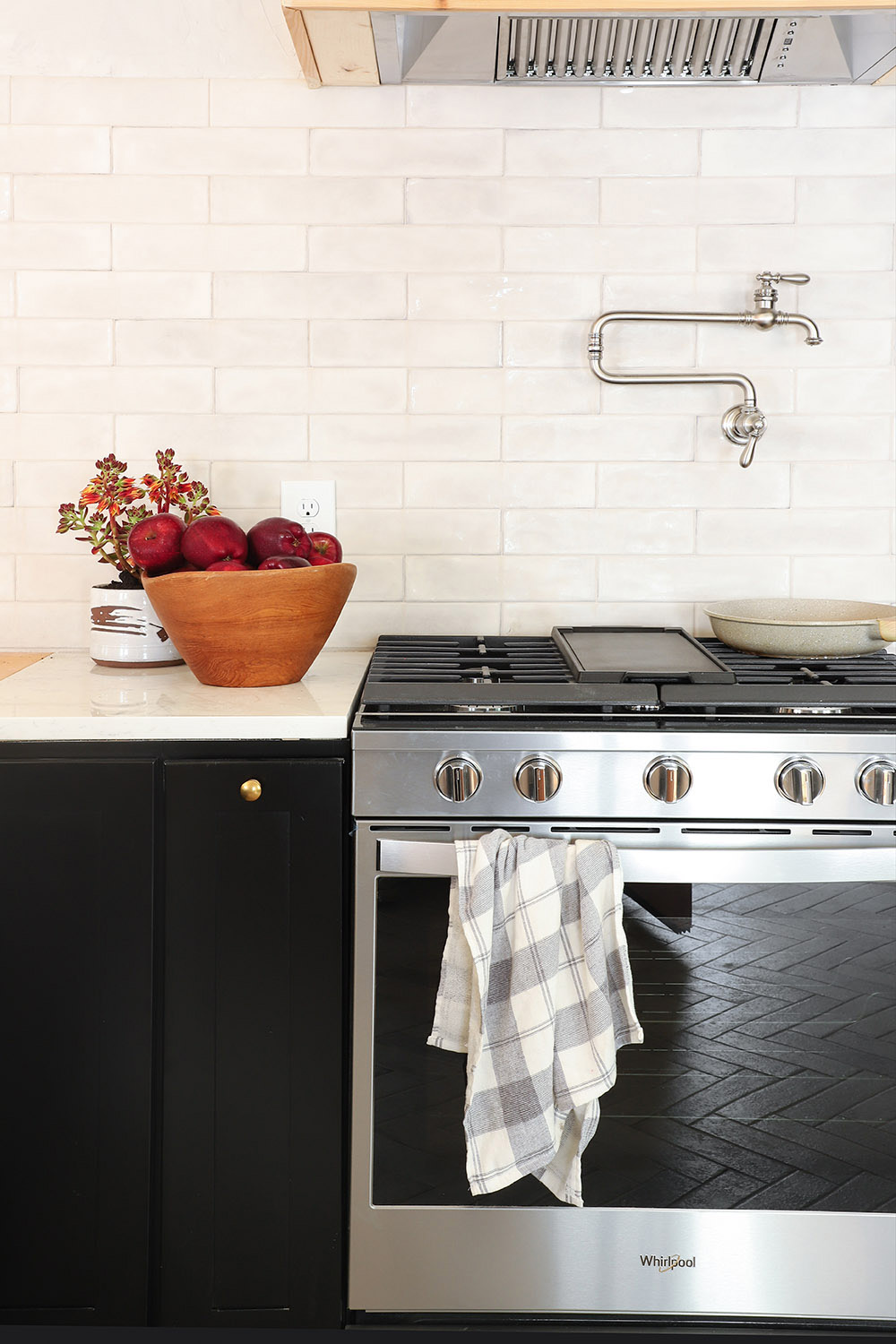 A pot filler on a tile wall sits above a new stainless steel slide-in gas range.