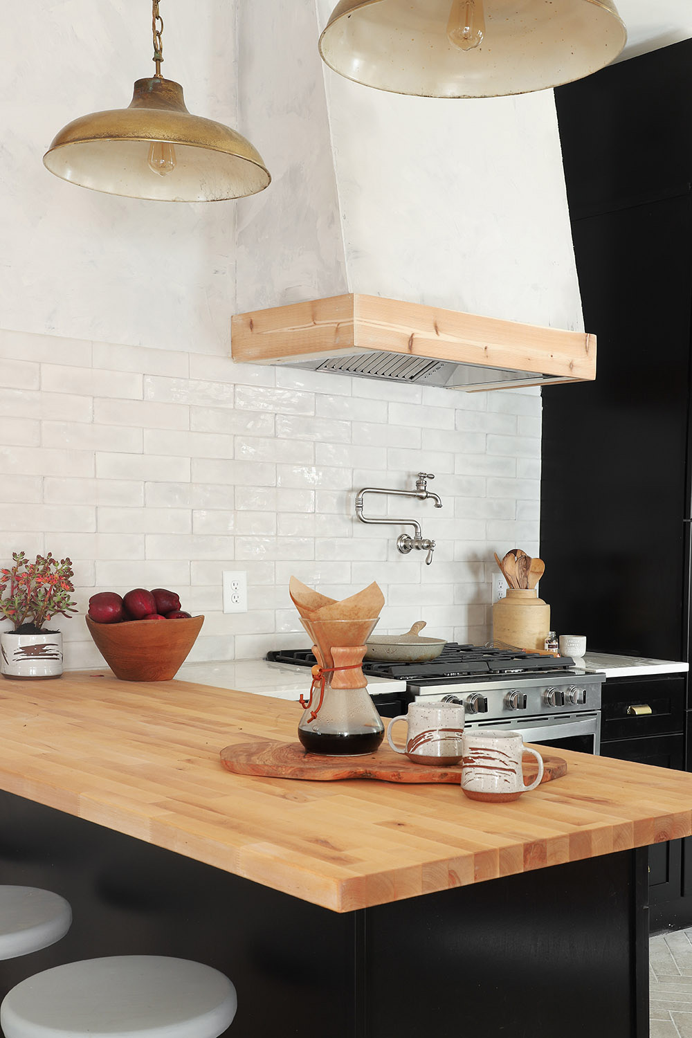 A wall mount range hood with wood accent cover around it.