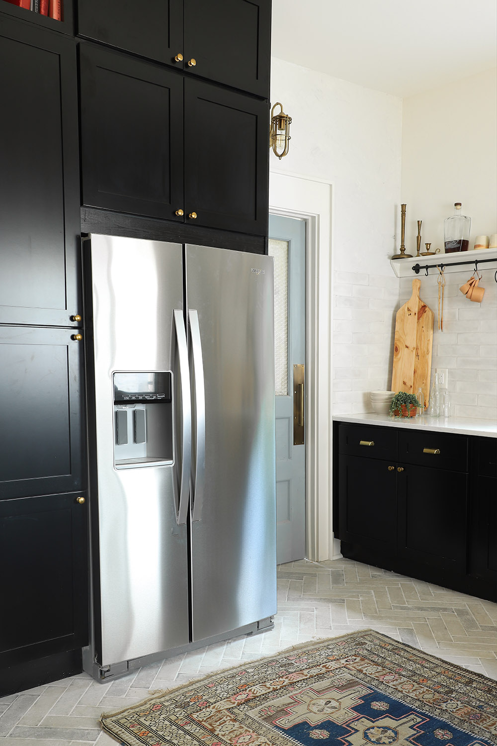 A counter-depth stainless steel refrigerator nestled between black cabinets.