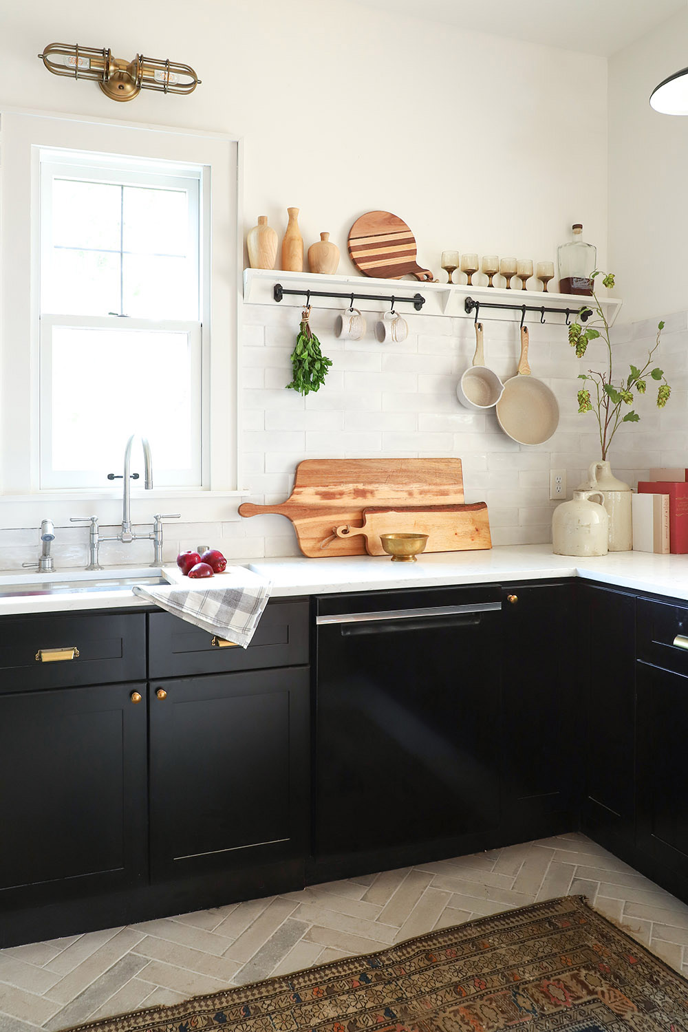 A black dishwasher and black cabinets with gold hardware.