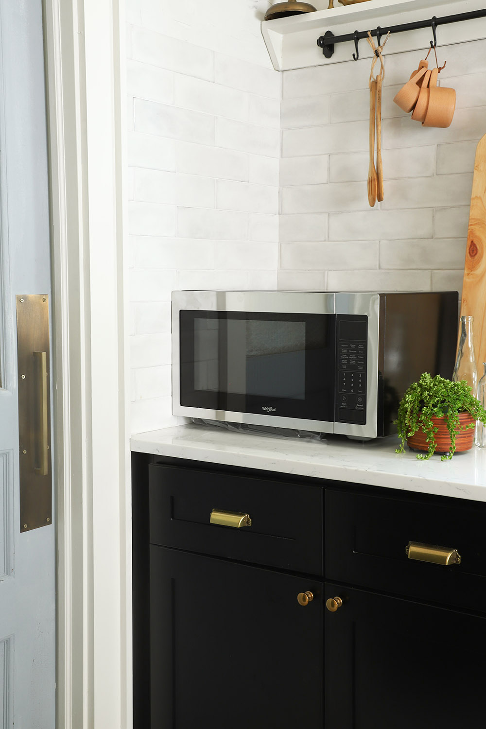 A stainless steel countertop microwave sits in the corner of a kitchen.