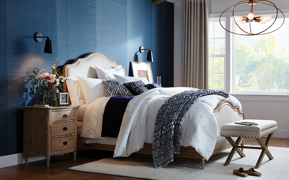 A bedroom featuring a bold blue accent wall behind the bed.