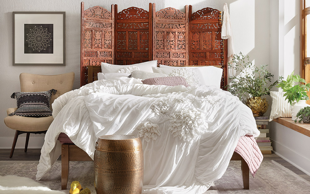 An intricately carved room separator is cleverly used as a headboard for a bed that is draped in comfy textiles.