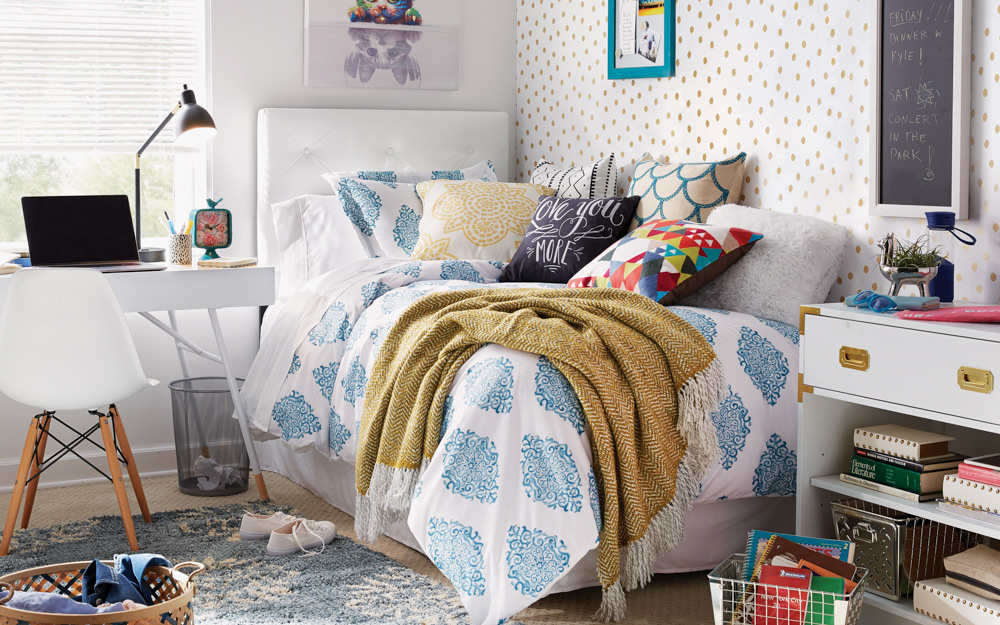 A bedroom with a writing desk, fun wall art and a brightly decorated twin bed is perfect for a teen.