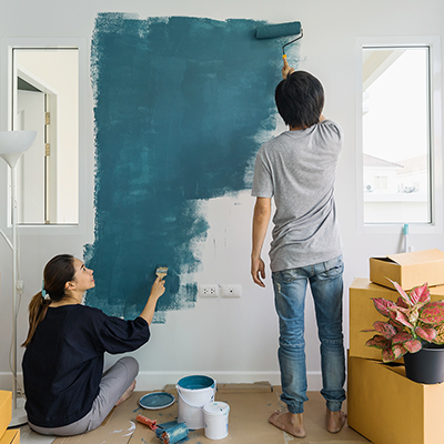 two people painting a white interior wall blue