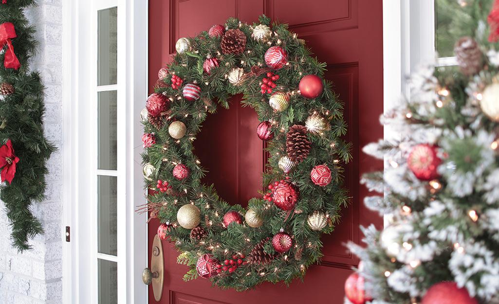 An artificial wreath hanging on a red door.