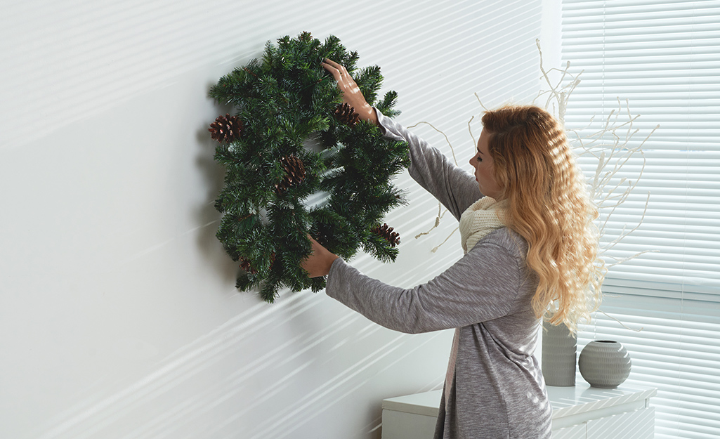 Woman hanging up a wreath.