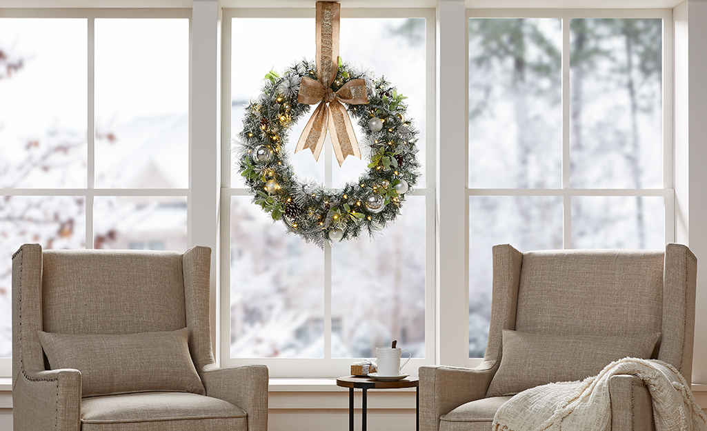 White and gold holiday wreath hanging in a window indoors