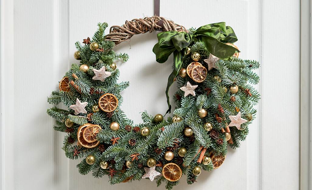 A hanging fresh-cut wreath with dried fruit ornaments