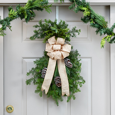 Holiday wreath with gold ribbon on front door