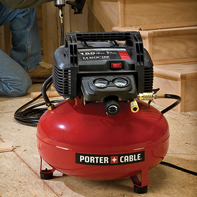 A portable air compressor in an unfinished room.