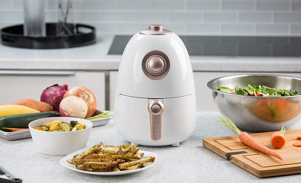 A white compact air fryer sits on a kitchen counter near salad ingredients.