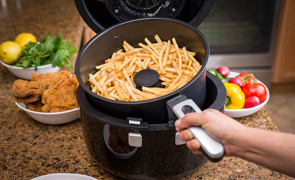 French fries sit in a paddle-type air fryer on a counter alongside fried chicken and vegetables.