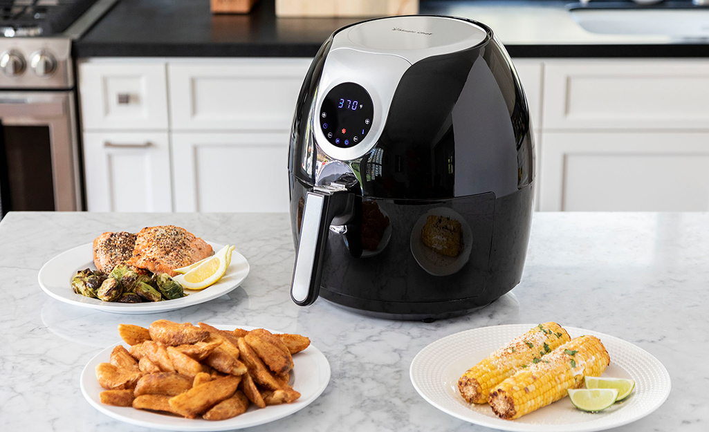 An air fryer with a digital screen sits on a counter next to salmon filets, steak fries and corn on the cob.