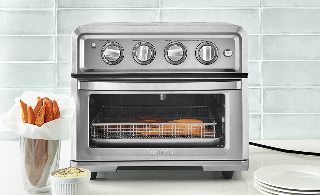 A combination air dryer/toaster oven sits on a counter next to sweet potato fries.