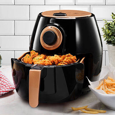 Chicken nuggets sit in a black air fryer on a white kitchen counter next to a bowl of French fries.