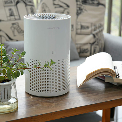 An air purifier sits on a living room table.