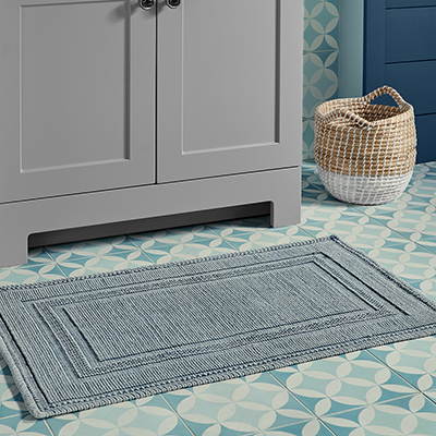 A grey bath rug sits in front of a bath vanity.
