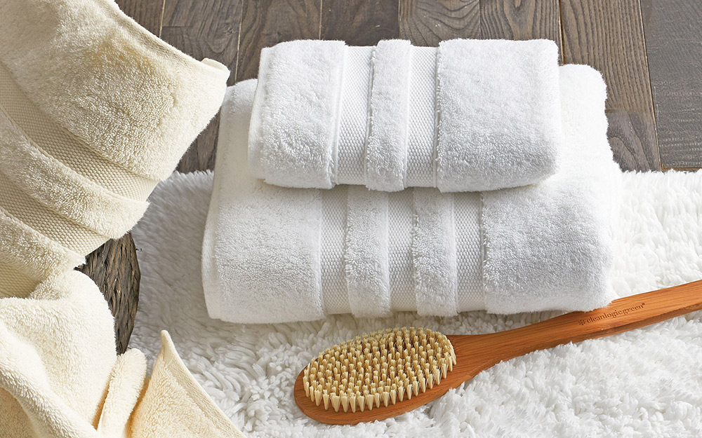 Egyptian cotton towels next to a bath brush.