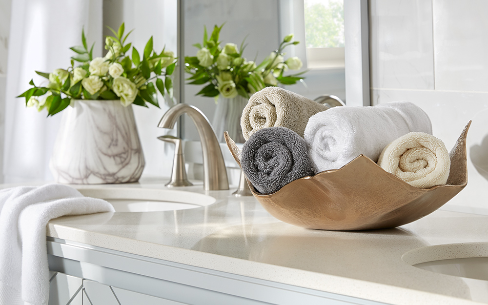 Towels in a brass bowl sitting on a vanity.