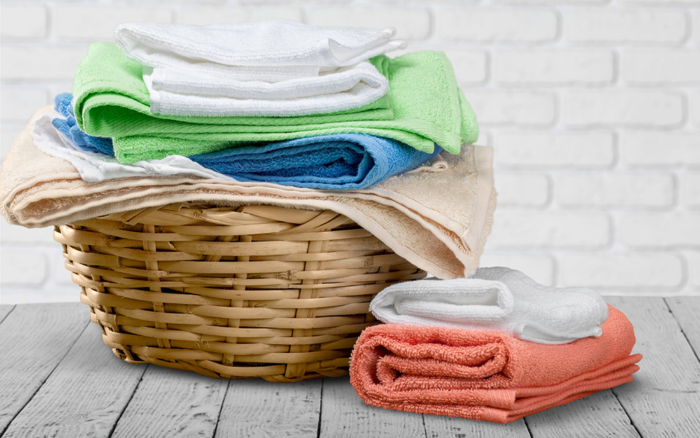 Towels piled in a laundry basket.