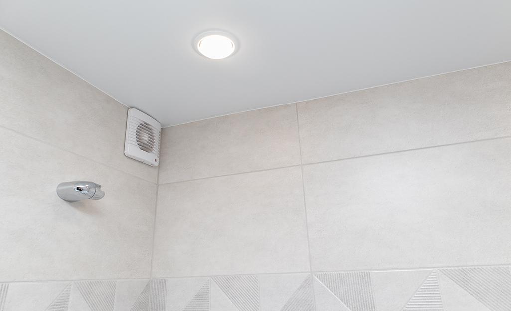 A wall bath fan in the top corner of a bathroom.