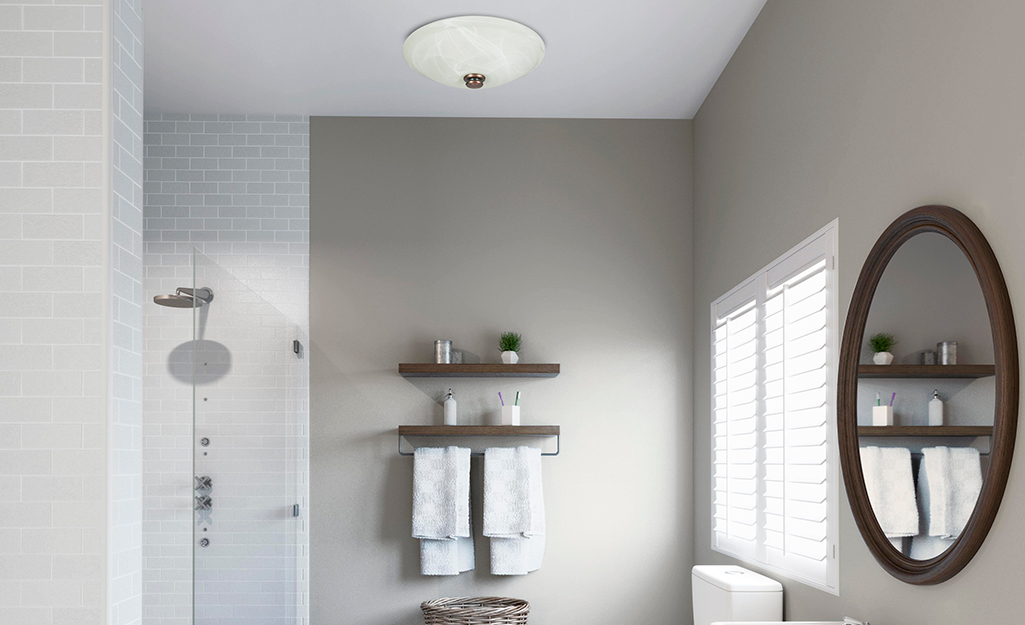 A decorative bathroom fan with a built-in light and glass globe.