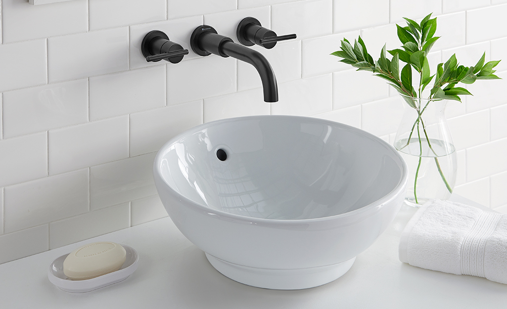 White raised sink installed under a black wall mount faucet.