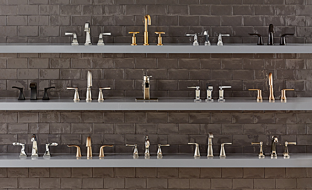 Three shelves holding a display of bathroom faucets in different styles and finishes.