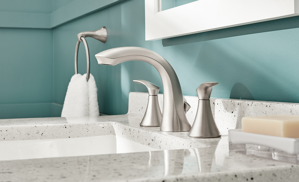 A nickel bathroom faucet with a white sink and black and white countertop.