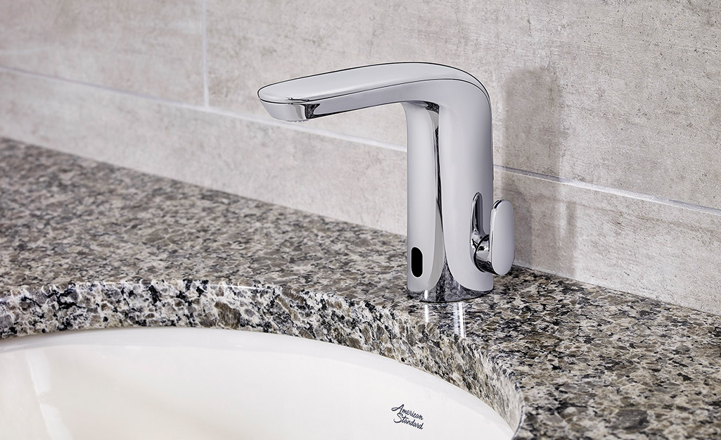 A touchless bathroom faucet with a white sink and black and white countertop.