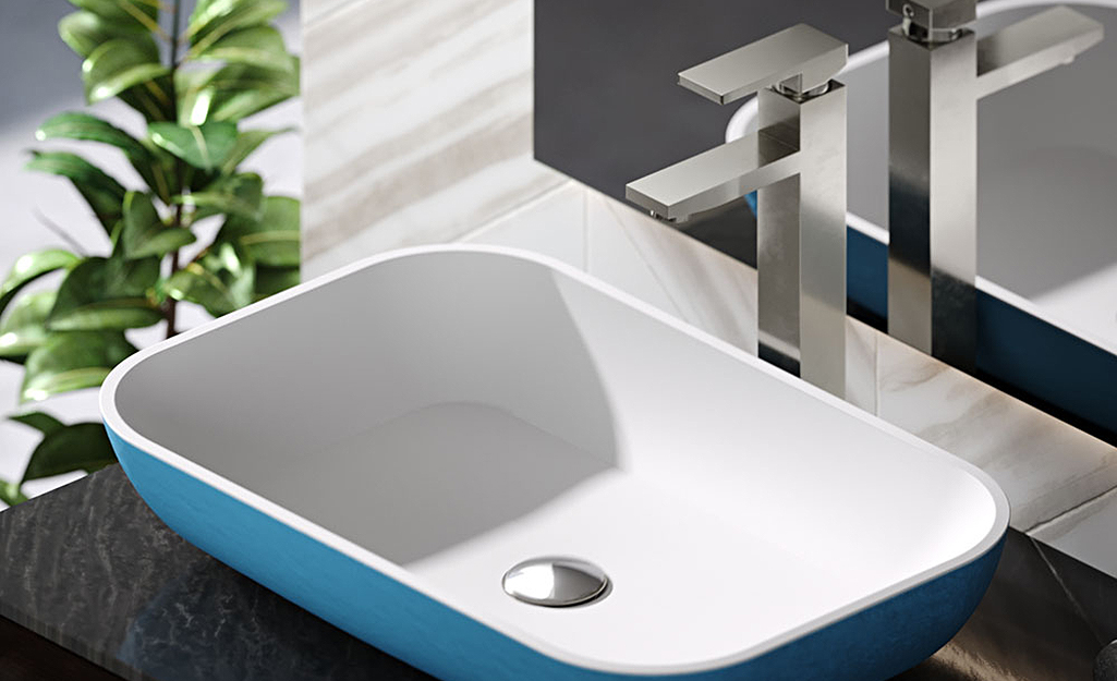 Vessel faucet over a blue and white raised sink bowl.